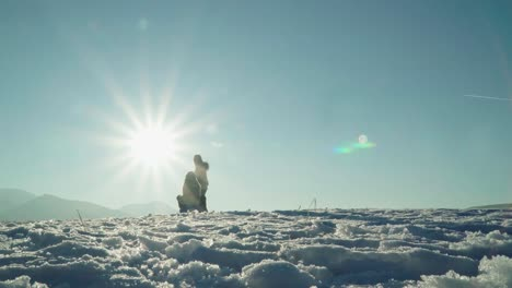 Wintermother-Rolls-The-Child-On-A-Sled-Against-Sunlight