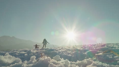 Mother-Rolls-The-Daughter-Child-On-A-Sled-Against-Sunlight-Lens-Flare