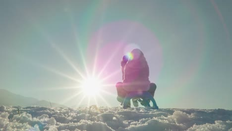 Mother-Rolls-The-Girl-Child-On-A-Sled-Against-Sunlight