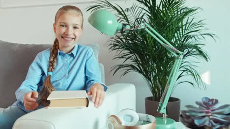 Portrait-Cheerful-Girl-9-Years-Old-Holds-In-Her-Hands-Book-And-Smiling-At-Camera