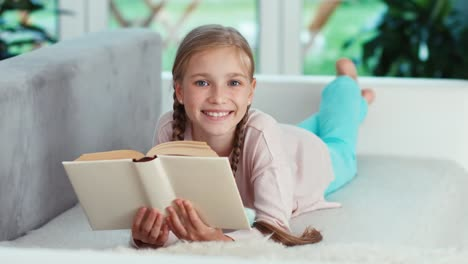 Portrait-Cheerful-Girl-9-Years-Old-Reading-Book-And-Lying-On-The-Sofa