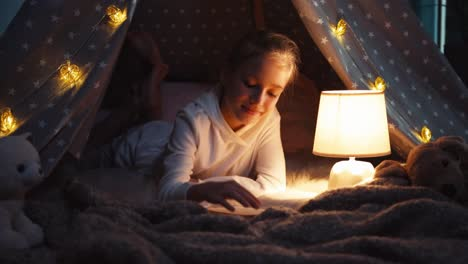 Portrait-Cheerful-Girl-9-Years-Old-Reading-Book-At-Night-In-The-Wigwam