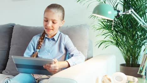 Portrait-Cheerful-Girl-9-Years-Old-Using-Tablet-PC-Sitting-On-Sofa