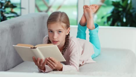 Portrait-Cheerful-Girl-9-Years-Relaxing-With-Book-On-The-Sofa-In-The-Living-Room