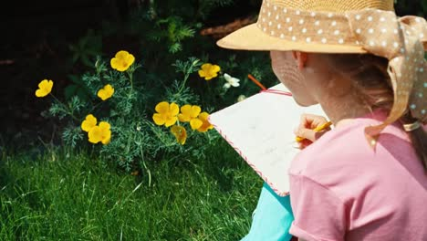 Portrait-Child-In-Straw-Hat-Aged-8-Writing-In-Notebook-And-Sitting-On-The-Grass