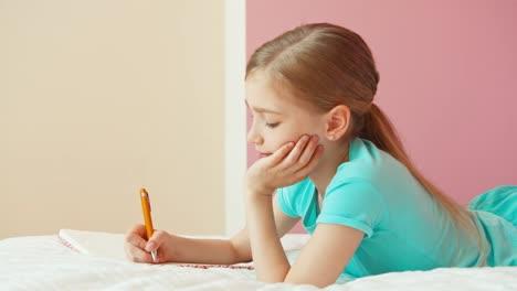 Retrato-Linda-Chica-De-9-Años-Escribiendo-En-El-Cuaderno-Y-Acostada-En-La-Cama