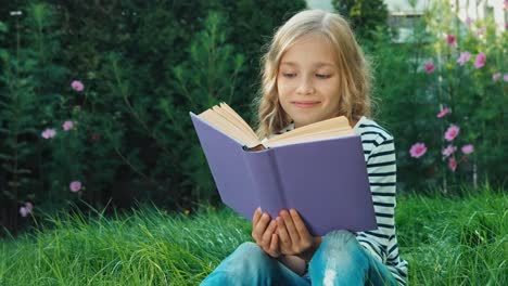 Portrait-Girl-8-Aged-Reading-Book-And-Sitting-On-The-Green-Grass-Dolly-Shot