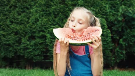 Portrait-Girl-Child-Bites-A-Watermelon-With-Big-Eyes-Outdoors
