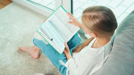 Portrait-Girl-Child-Sitting-On-The-Carpet-Reading-Textbook-And-Smiling-At-Camera