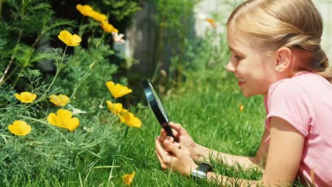 Portrait-Girl-Looking-Through-Magnifying-Glass-At-Flower-Kid-Lying-On-The-Grass