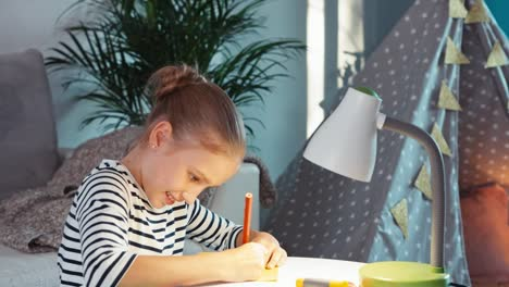 Portrait-Girl-Paints-With-Pencils-In-Notebook-At-The-Coffee-Table-And-Smiling