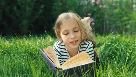 Portrait-Girl-Reading-Book-In-The-Grass-And-Smiling-At-Camera-Dolly-Shot