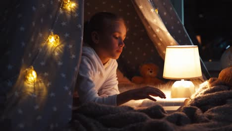 Portrait-Girl-Reading-Book-Lying-In-Wigwam-At-Night