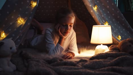 Portrait-Girl-Relaxing-In-Wigwam-At-Night-Dolly-Shot