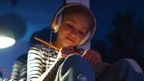 Retrato-Chica-Algo-Dibujando-En-El-Cuaderno-Y-Escuchando-Música-En-Auriculares