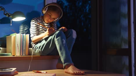 Portrait-Girl-Something-Writing-In-Notebook-And-Listening-Music-In-Headphones