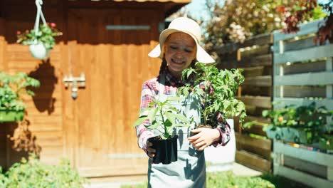 Portrait-Little-Farmer-Girl-Offering-Vegetable-Seedlings-At-Camera