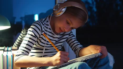 Portrait-School-Girl-Writing-In-Exercise-Book-And-Listening-Music-In-Headphones