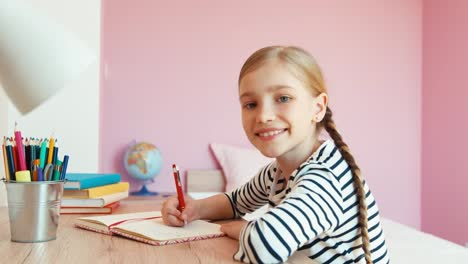 Portrait-School-Girl-Writing-In-Notebook-When-She-Doing-Homework