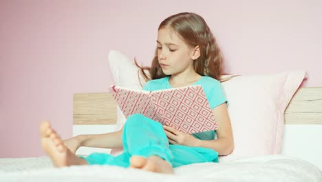 Schoolgirl-Reading-Book-On-Bed-Using-Cellphone-And-Laughing