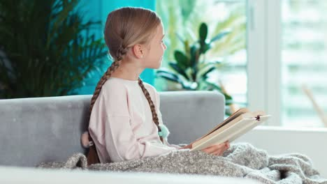 Smiling-Girl-Reading-Book-Sitting-On-The-Sofa-And-Looking-At-Window