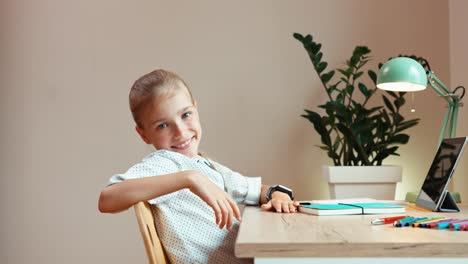Student-Blonde-Girl-8-Aged-Sitting-At-The-Desk-In-The-Bedroom-And-Smiling