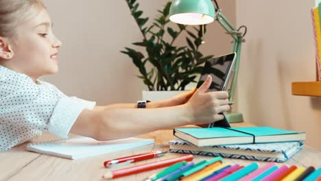 Student-Girl-8-Aged-Writing-In-Notebook-And-Using-Tablet-PC-At-The-Desk