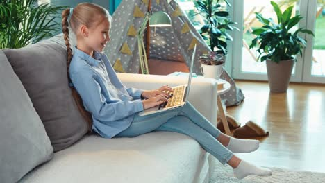 Student-Girl-9-Years-Old-Using-Laptop-PC-Sitting-On-Sofa-In-Living-Room