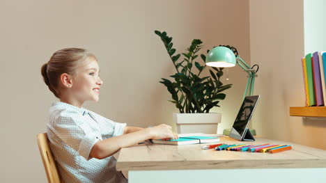Student-Girl-Sitting-At-The-Desk-At-Home-And-Smiling-At-Camera