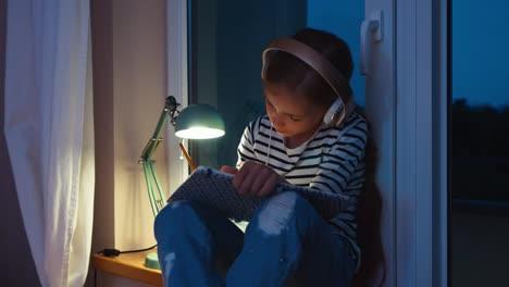 Girl-Something-Writing-In-Notebook-And-Listening-Música-In-Headphones