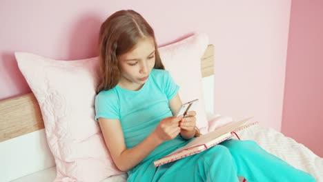 Studentin-Die-Etwas-Im-Lehrbuch-Schreibt-Und-Smartphone-Sitz-Verwendet
