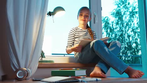 Student-Reading-Book-And-Sitting-On-The-Window-Sill-At-Her-Room