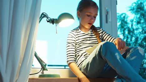 Thoughtful-Schoolgirl-Using-Textbook-On-The-Windowsill