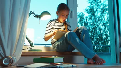 Thoughtful-Student-Using-Textbook-On-The-Windowsill