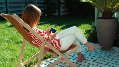 Woman-Using-Cell-Phone-And-Relaxing-On-Patio-At-Home