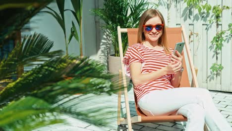 Woman-Using-Cell-Phone-On-Patio