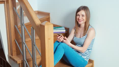 Woman-Using-Cell-Phone-On-The-Stairs-And-Smiling-At-Camera