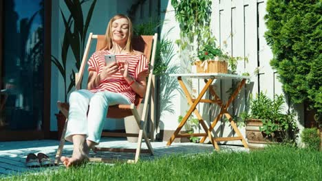 Woman-Using-Cell-Phone-Online-And-Relaxing-On-Patio-At-Home