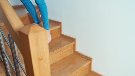 Woman-Using-Cell-Phone-Sitting-On-The-Stairs-Indoors