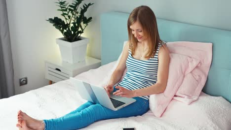 Woman-Using-Laptop-On-The-Bed-At-Home-And-Smiling-At-Camera