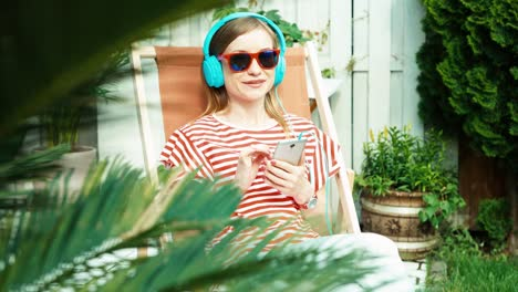 Young-Adult-Woman-Listening-Music-In-Headphones-And-Using-Cell-Phone-At-Sunny