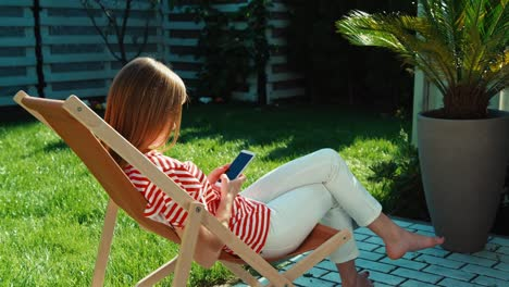 Young-Adult-Woman-Making-Selfie-Photo-On-The-Armchair-Outdoors