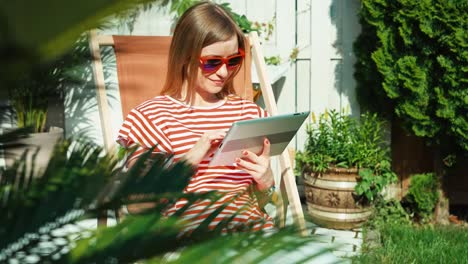 Young-Adult-Woman-Using-Tablet-PC-At-Sunny-Day-Outdoors-In-Patio