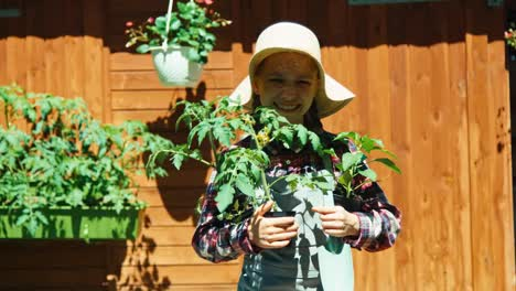 Young-Farmer-Girl-Hold-Seedlings-Of-Tomato-And-Paprika-And-Smiling-At-Camera