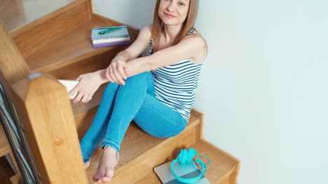Young-Woman-Using-Cell-Phone-On-The-Stairs-And-Smiling-Top-View