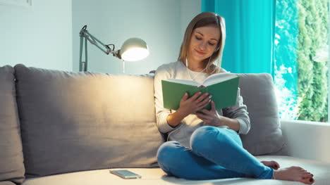 Mujer-Joven-Con-Libro-Mirando-A-La-Cámara-En-La-Sala-De-Estar
