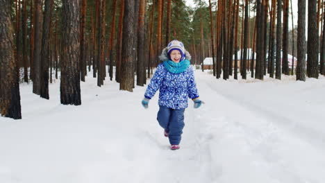 Playful-Young-Girl-Walking-Through-Snowy-Woodland