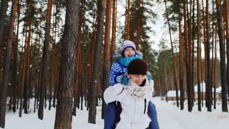 Active-Mom-Carrying-Daughter-Through-Snowy-Woodland