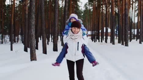 Mother-Carries-He-Daughter-Playfully-Through-Snowy-Woods