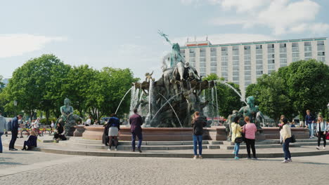 Tourists-And-Locals-Stroll-Around-The-Famous-Neptune-Fountain-In-Berlin